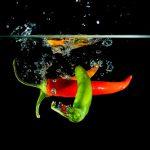 Chillischoten fallen ins Wasser schöne Luftblasen