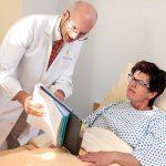Chefarzt-Visite, Chefarzt spricht mit Patientin