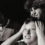 Elisabetta-Theaterfoto, 3 Personen, Frau im Vordergrund rauft sich die Haare
