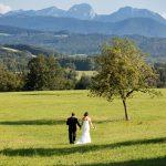 Hochzeitsfoto-07, Paar auf Wiese von hinten, im Hintergrund Berge