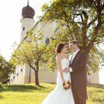 Hochzeitsfoto-08, Paar haelt sich vor Kirche zaertlich