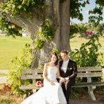 Hochzeitsfoto-09, Paar sitzt auf Bank vor Baum