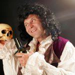 Joerg-Kuenstlerportrait, Mann in Barockkleidung haelt Totenkopf und Weinglas