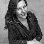 Andrea-Kuenstlerportrait, Frau mit langen Haaren und Jeansoverall schaut in die Kamera