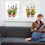 Produktfoto-Fensterbild, Zimmer mit Fenster, Blumen aufgeklebt, Frau auf SOFA